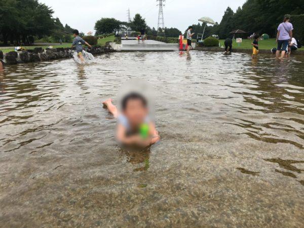 水遊び広場で寝る子供の写真